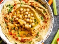 Closeup of hummus in dish topped with paprika, olive oil, parsley and chickpeas, crudités on the side.