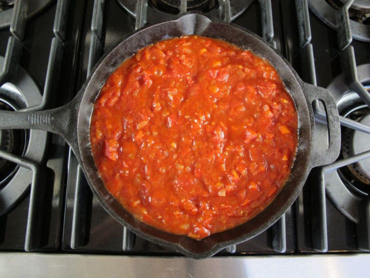 Diced tomatoes, pepper and onion sautéing in black cast iron frying pan on stovetop.