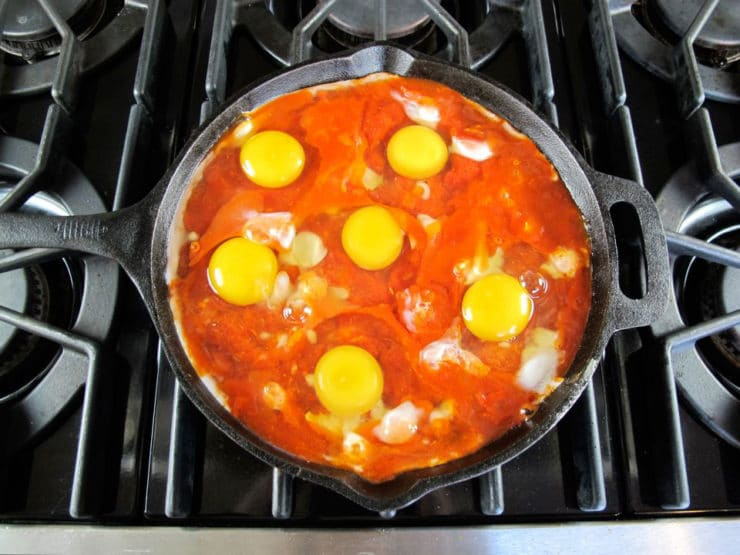 Eggs cooking on top of tomato sauce with pepper and onion sautéing in black cast iron frying pan on stovetop.