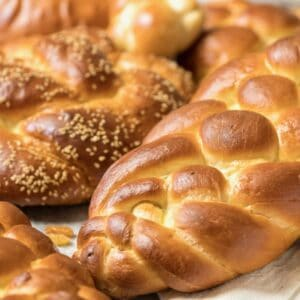 Several loaves of braided challah bread - multiple braiding styles - in a pretty pile on countertop.