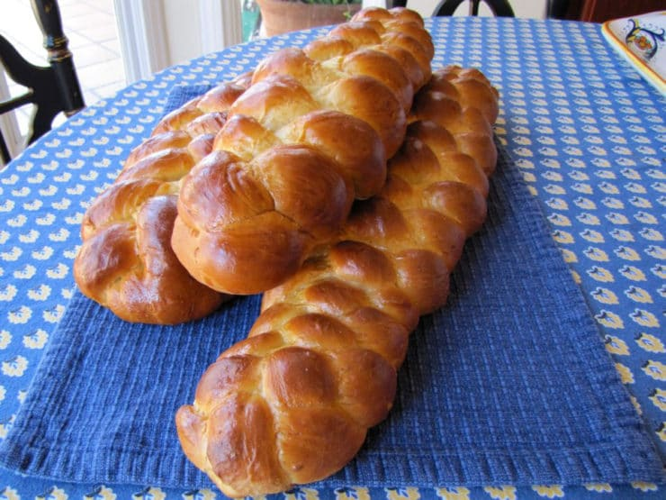 Three braided challah loaves on the table.