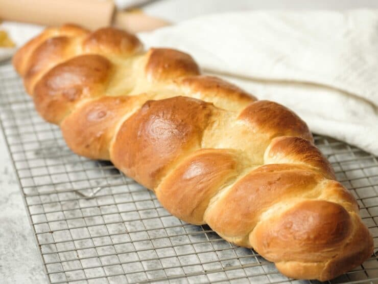 Front view horizontal shot - three strand challah braid fully baked, cooling on wire cooling rack wtih cloth napkin in background.