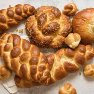 Overhead shot - multiple challah braids - three strand, four strand, round braid, turban challah, and challah rolls, on marble countertop with cloth napkin beneath.