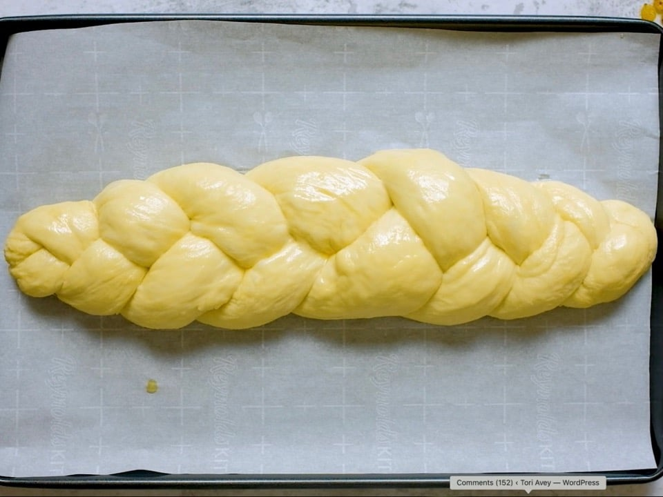 Overhead shot of braided challah dough with shiny egg wash on parchment-lined baking sheet.