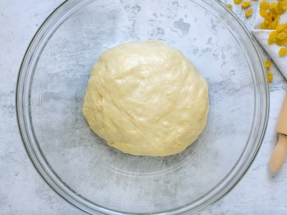Dough resting in a smooth ball in oiled glass bowl.