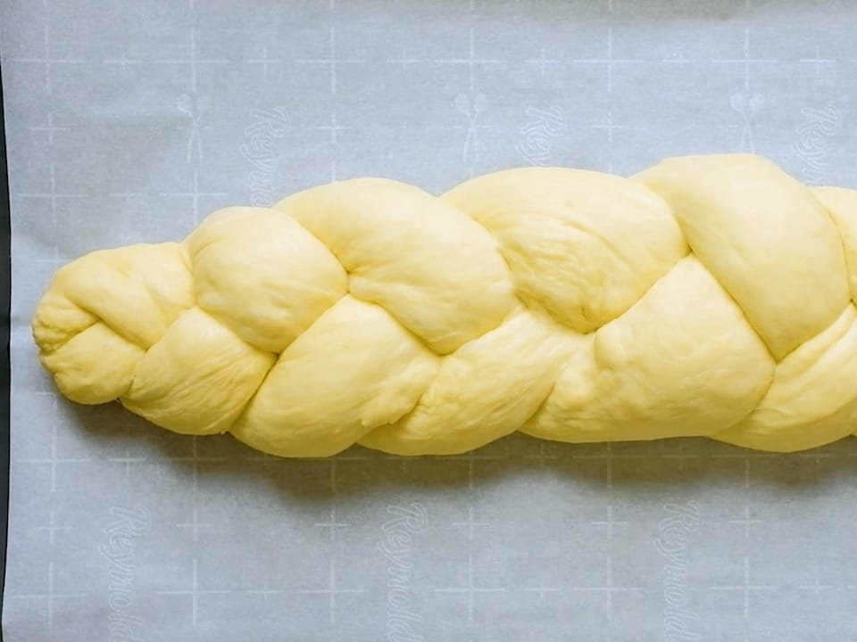 Braided challah dough on parchment-lined baking sheet.