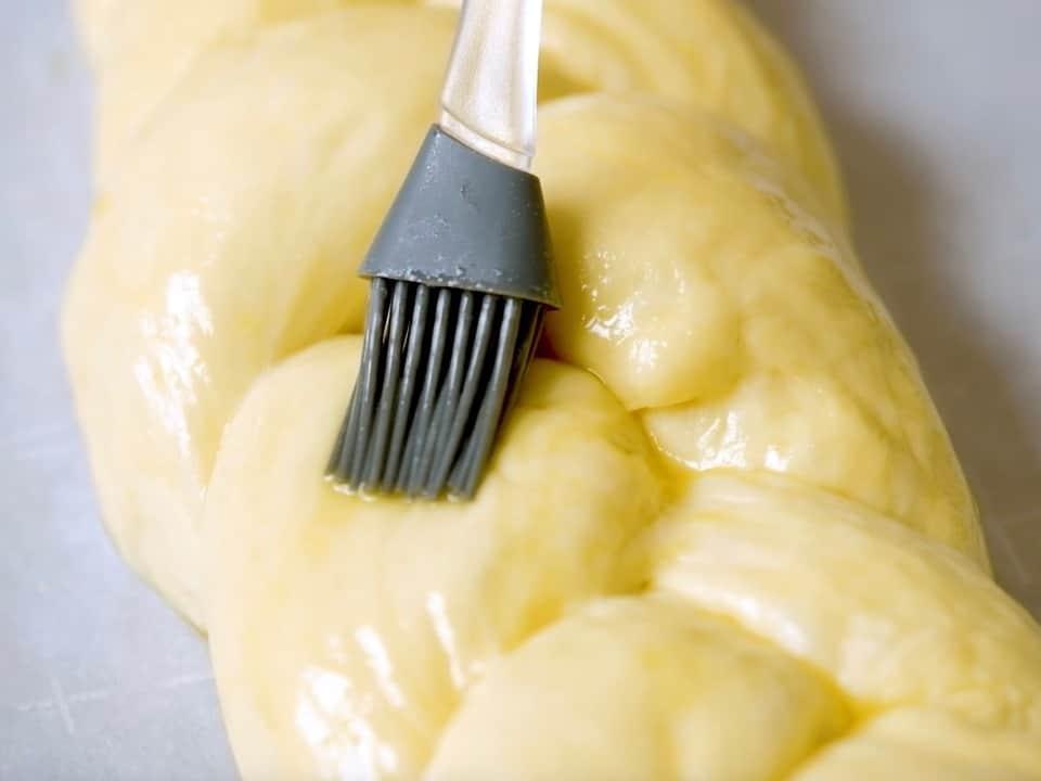 Silicone brush brushing challah braid with egg wash.