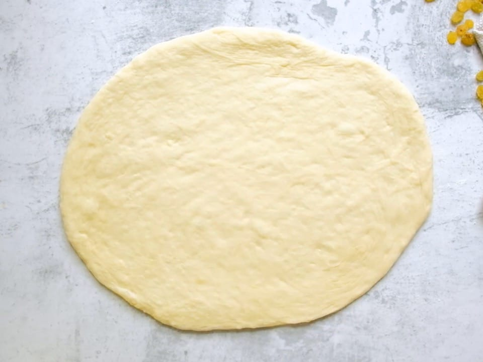 Overhead shot of challah dough that has been rolled into an oval shape.