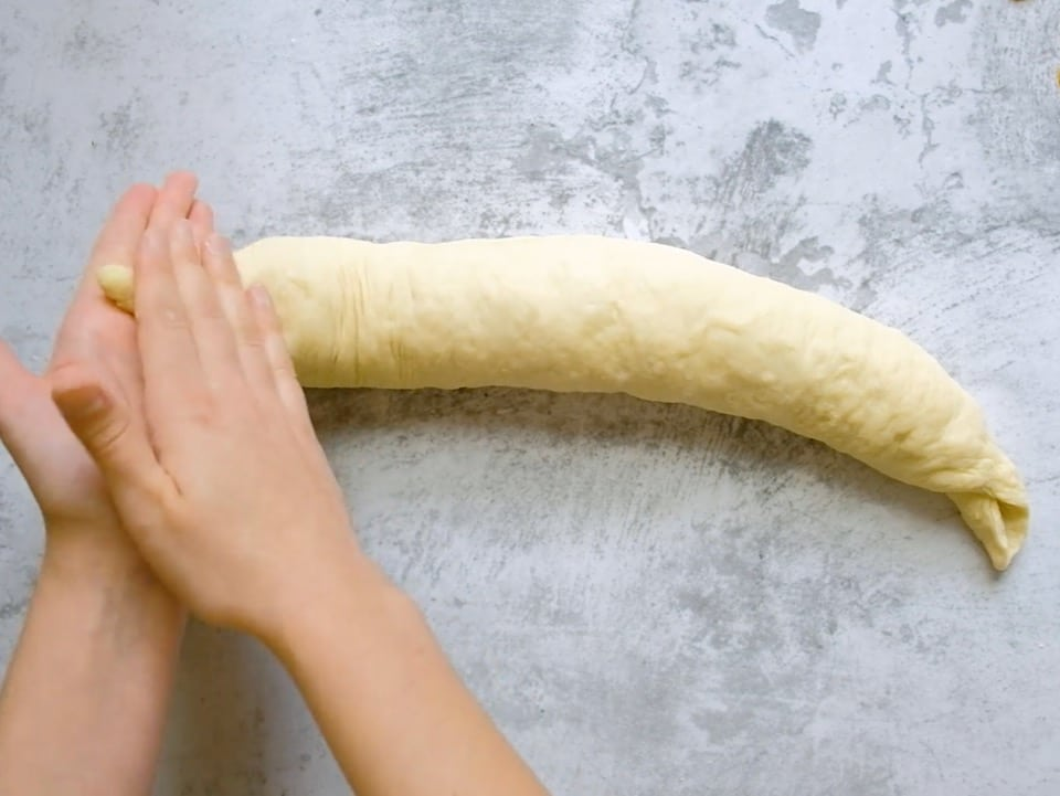Overhead shot of two hands rolling the end of the challah dough strand into a taper.