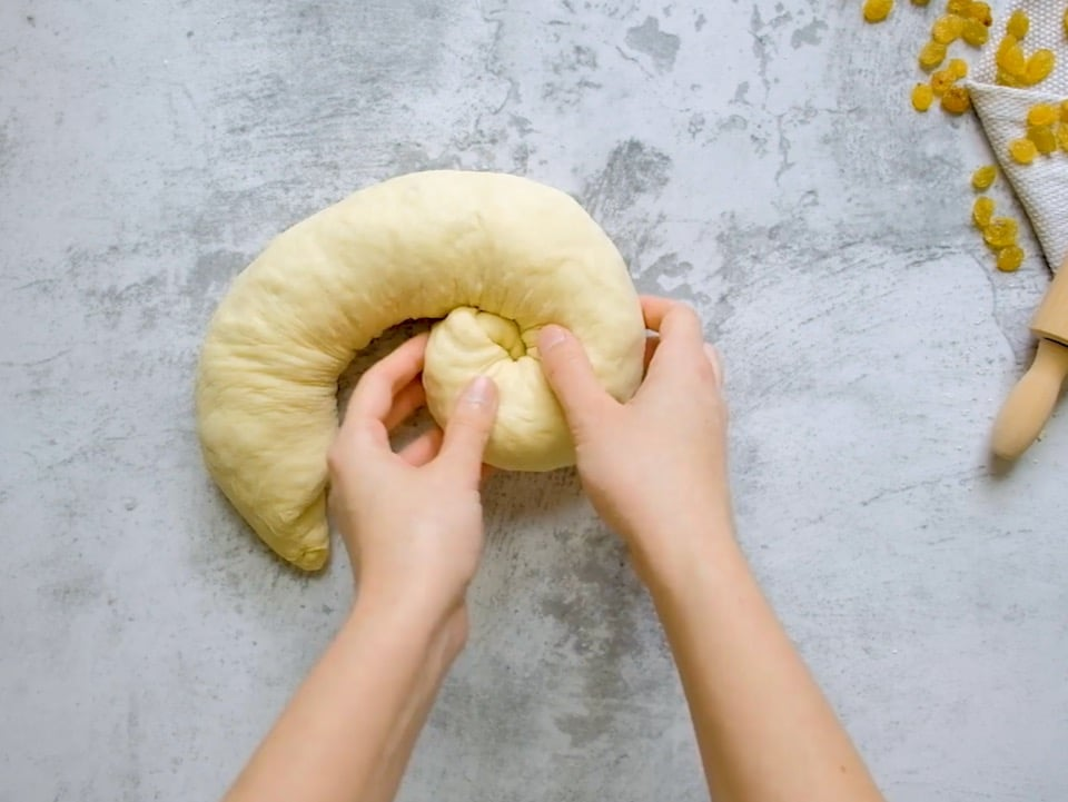 Overhead shot of two hands rolling a strand of challah dough into a coil shape, known as a turban challah.