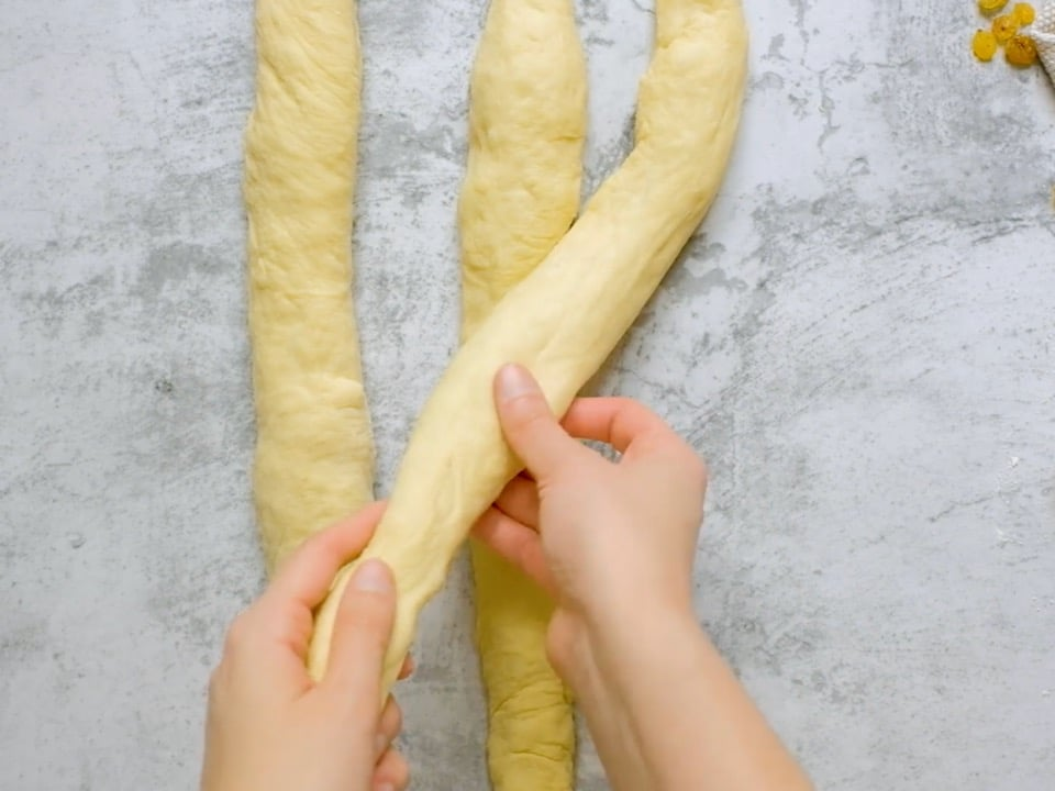 Overhead shot of three equal strands of challah laying next to each other. Two hands are crossing the strand on the right over the strand in the center.