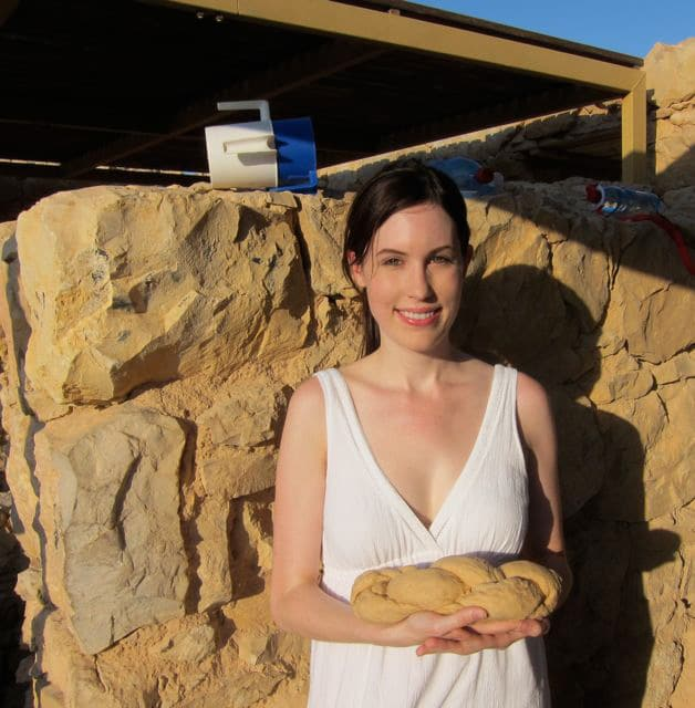 A photo of Tori Avey on top of the historical fortress Masada, holding braided challah dough.