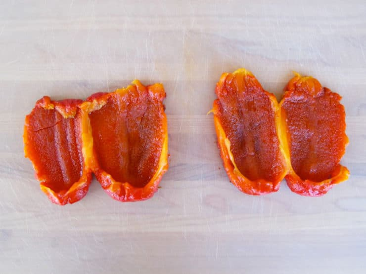Roasted red peppers sliced open in half.