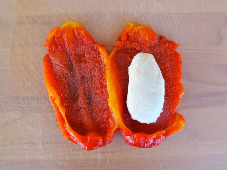 Goat cheese placed on red pepper half.