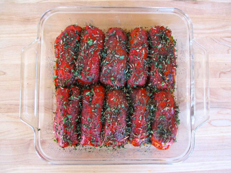 Herbs sprinkled over stuffed peppers in a baking dish.