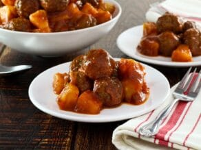 Sweet and sour meatballs on a plate with cloth napkin beside, more meatballs in dish in background.