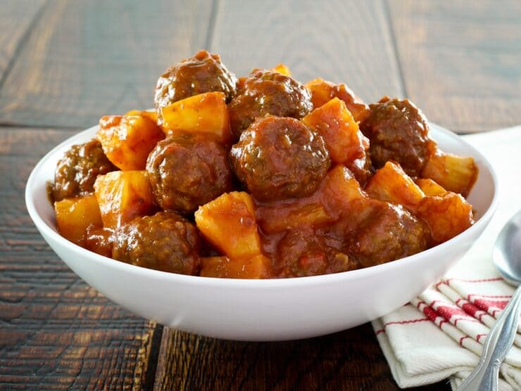Bowl of sweet and sour meatballs with pineapple.