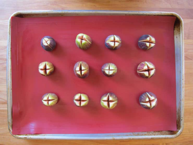 Figs cut open in an X, on a lined baking sheet.
