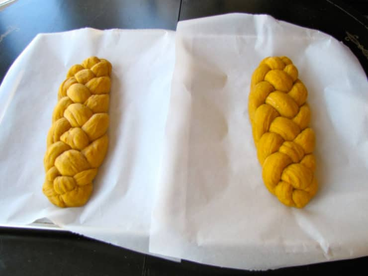 Two braided challah loaves on parchment lined baking sheets.