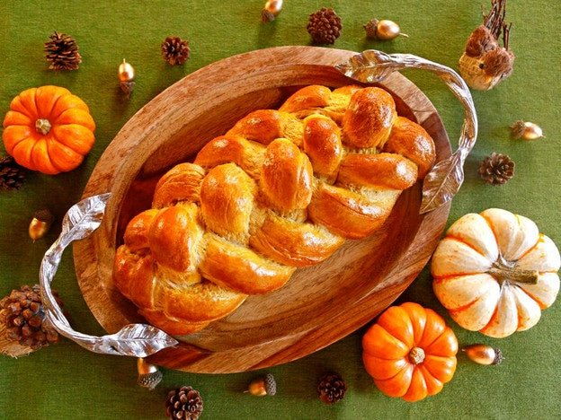 Golden baked Pumpkin Challah on top of a wooden platter with silver decorative handles on a green background. Small, decorative acorns, pine cones, and pumpkins are laying around the platter.