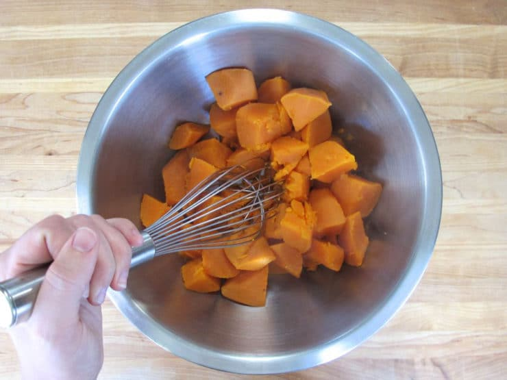 Mashing sweet potatoes in a mixing bowl.