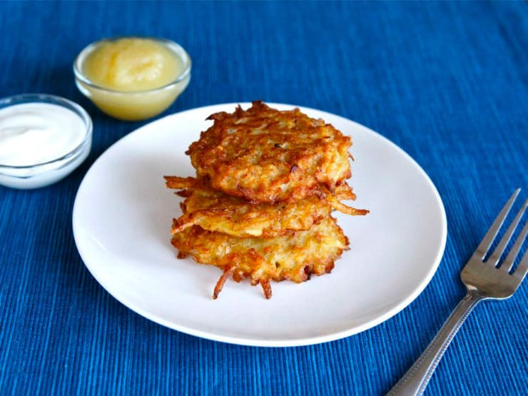 Pile of golden latkes on white plate with fork, on blue placemat with applesauce and sour cream.