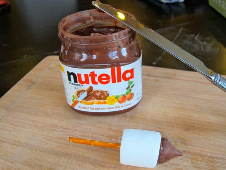 Jar of Nutella with candy dreidel in front and knife for spreading.