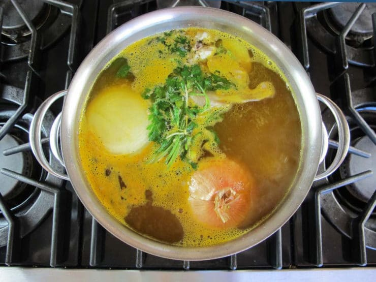 Turmeric and cilantro added to chicken in pot.