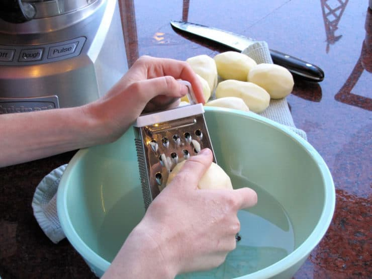 Hand grating peeled potatoes over an aqua-colored bowl next to a food processor, knife in background.