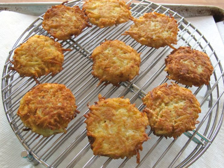 Potato latkes draining on a rack.