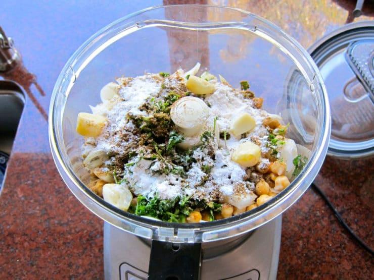 Food processor filled with falafel ingredients.
