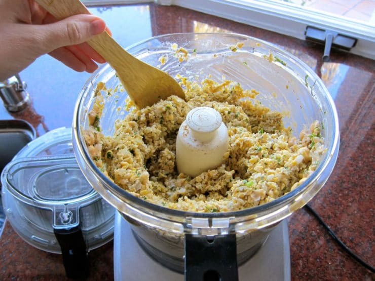 Falafel ingredients processed to a crumb-like texture in food processor, hand with wooden spoon scraping edges.
