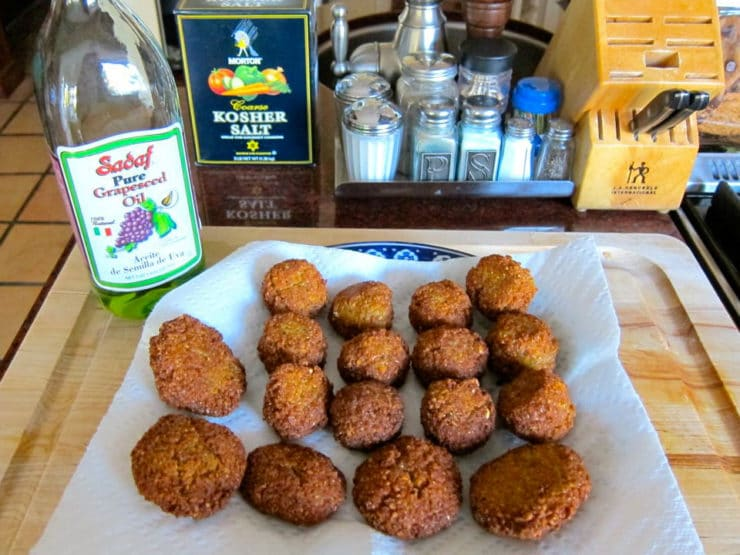 Falafel draining on paper towels with grapeseed oil.