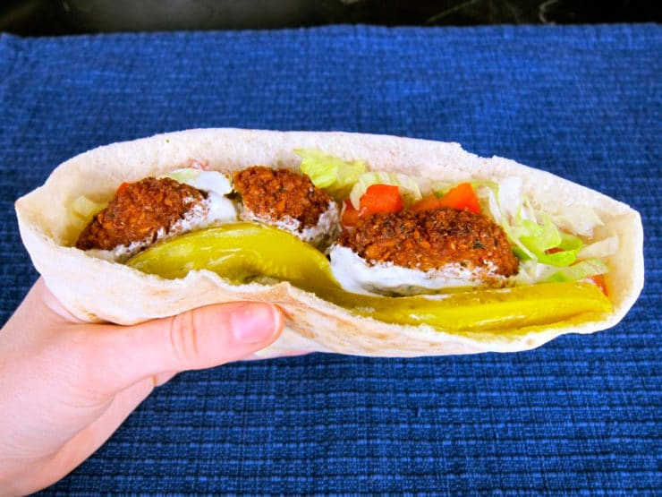 Falafel pita in hand with pickles, lettuce and tomatoes.