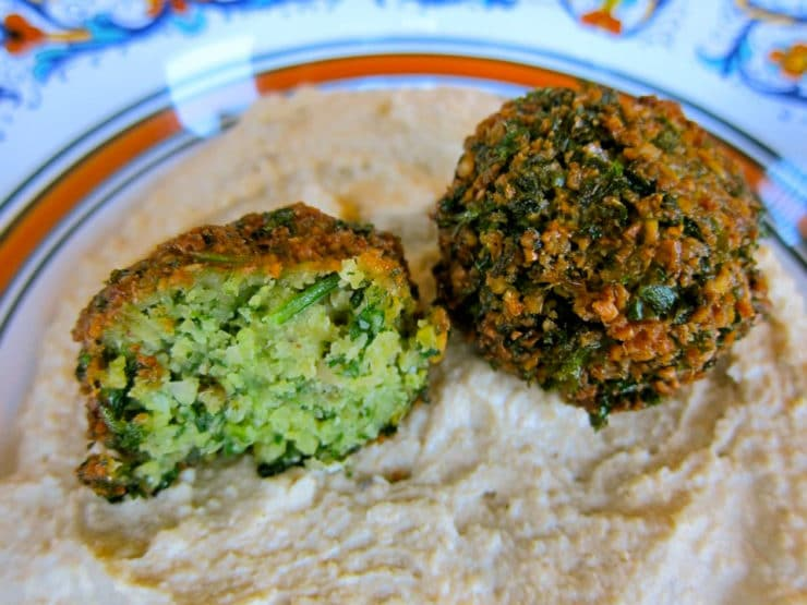 Herb green falafel balls on hummus.