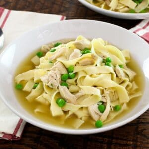 Horizontal shot - bowl of chicken with homemade noodles and sweet peas with cloth napkin and spoon on wooden background.