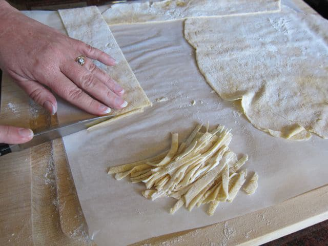 Cutting dried dough into strips.