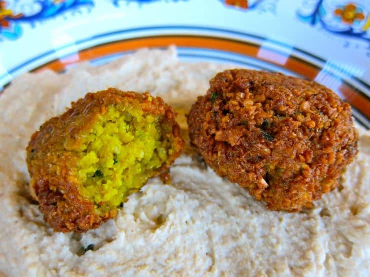 Yellow turmeric falafel balls on hummus.