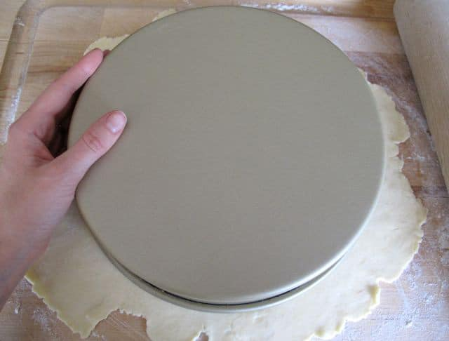 Tracing a cake pan onto rolled dough for a circle.