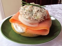 Whitefish salad on egg bagel with lox, cream cheese, and sliced onion