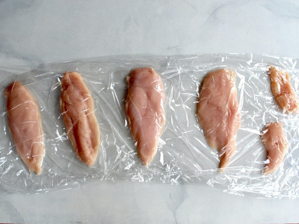 Four chicken breast halves and smaller tenderloin pieces between plastic wrap sheets on marble counter surface.