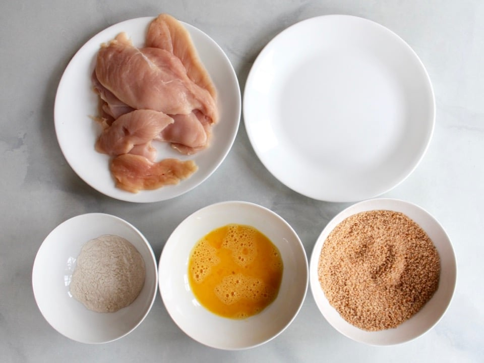 Five dishes - raw chicken breast halves, flour, beaten egg, breadcrumbs, and empty plate.