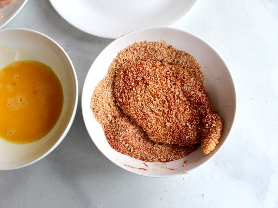 Chicken breast resting in dish of paprika sesame breadcrumbs, fully breaded.