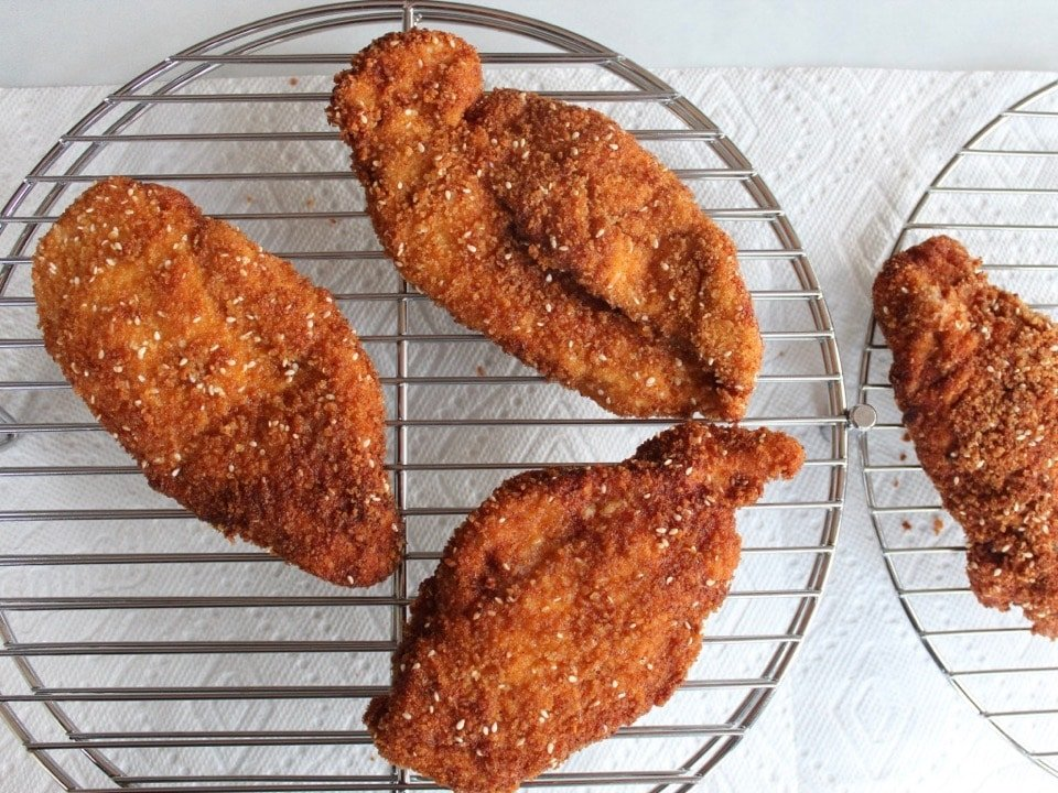 Fried golden schnitzels on rack with paper towels below.