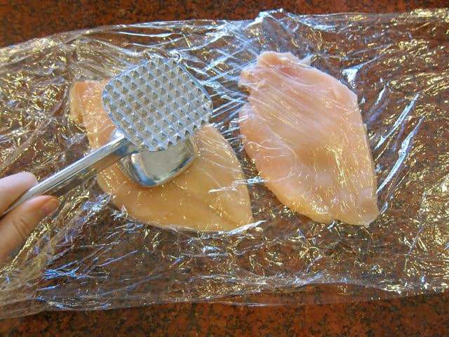 Pounding chicken breasts between layers of plastic wrap.