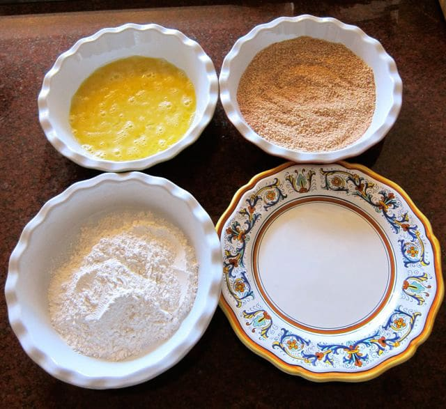 Flour, egg, and breading in small, shallow bowls.