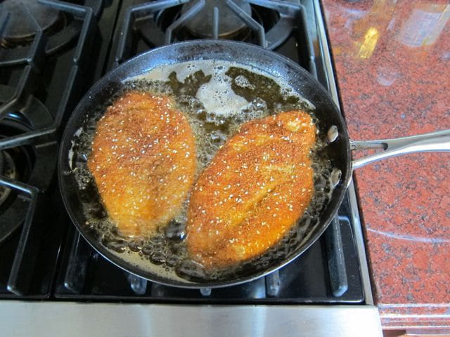 Frying chicken breasts in a skillet.