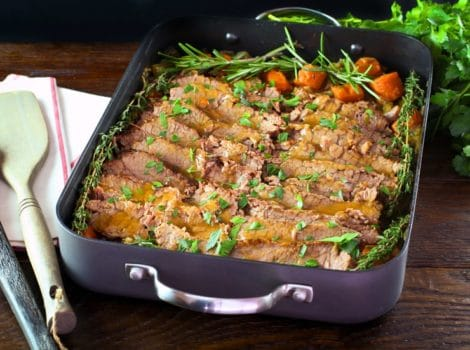 Roasting pan with cooked sliced brisket and carrots topped with fresh herbs, fresh parsley and cloth napkin on the side.