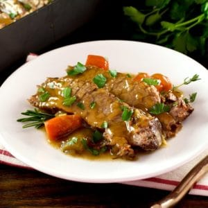 White plate with tender slices of savory herb braised brisket and carrots, topped with fresh herbs. Napkin, fork and fresh herbs in background with roasting pan of meat.
