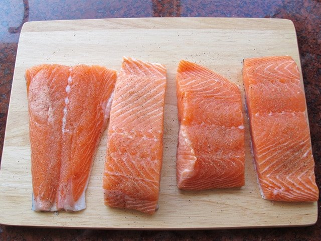Seasoning salmon fillets on a cutting board.